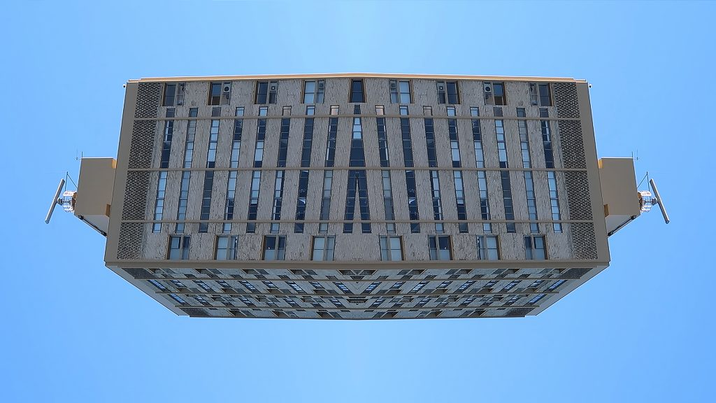 Collage with mirrored top part of building displayed horizontally against blue sky.